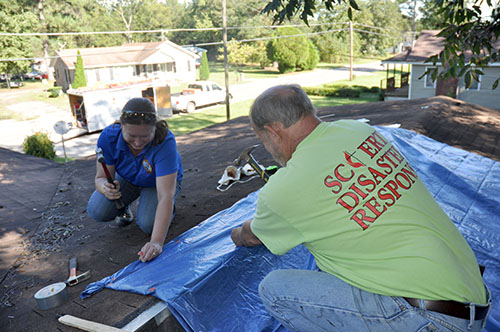 Sallie Clamp & Rev. Bob Allen of SC ERT tarp the roof of a damaged home in Holly Hill, SC