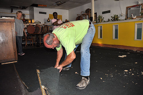 Rev. Bob Allen cutting out flooded carpet from a flooded building in Holly Hill, SC.